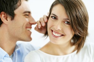 Closeup portrait of a handsome young man whispering in his wife ear